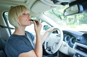 Lady putting on Lipstick while driving