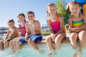 happy children sitting on side of pool