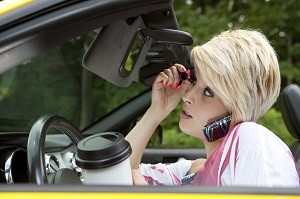 woman driving while talking on cell phone holding a cup of coffee and putting on makeup