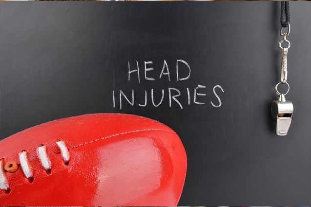 Head Injury written on chalkboard with football and coaches whistle
