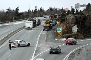 highway with stopped traffic and police officer routing others off at an exit