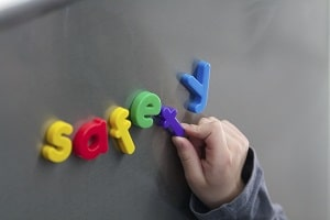 child spelling the word safety in brightly colored magnetic letters