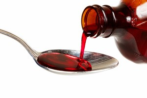 red cough syrup being poured into teaspoon