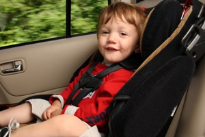 happy child in back seat of vehicle safely in car seat