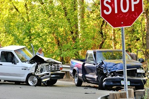 stop sign in foreground with two wrecked trucks in background