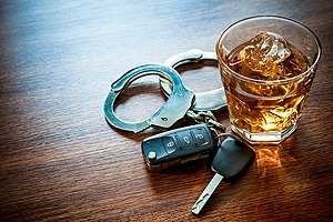 rocks glass of brown liquor on ice sitting on table next to car keys and pair of handcuffs