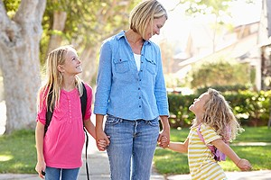 smiling woman walking on sidewalk hand in hand with two young girls