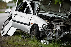 silver car on the side of the road badly damaged from car accident