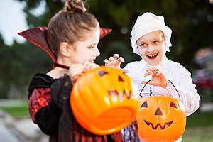happy children dressed in costumes trick or treating