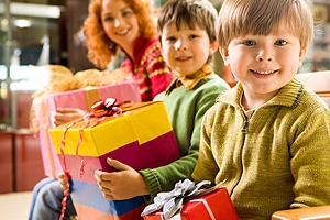 smiling children holding brightly wrapped presents