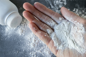 talcum powder spilled into hand from overturned container