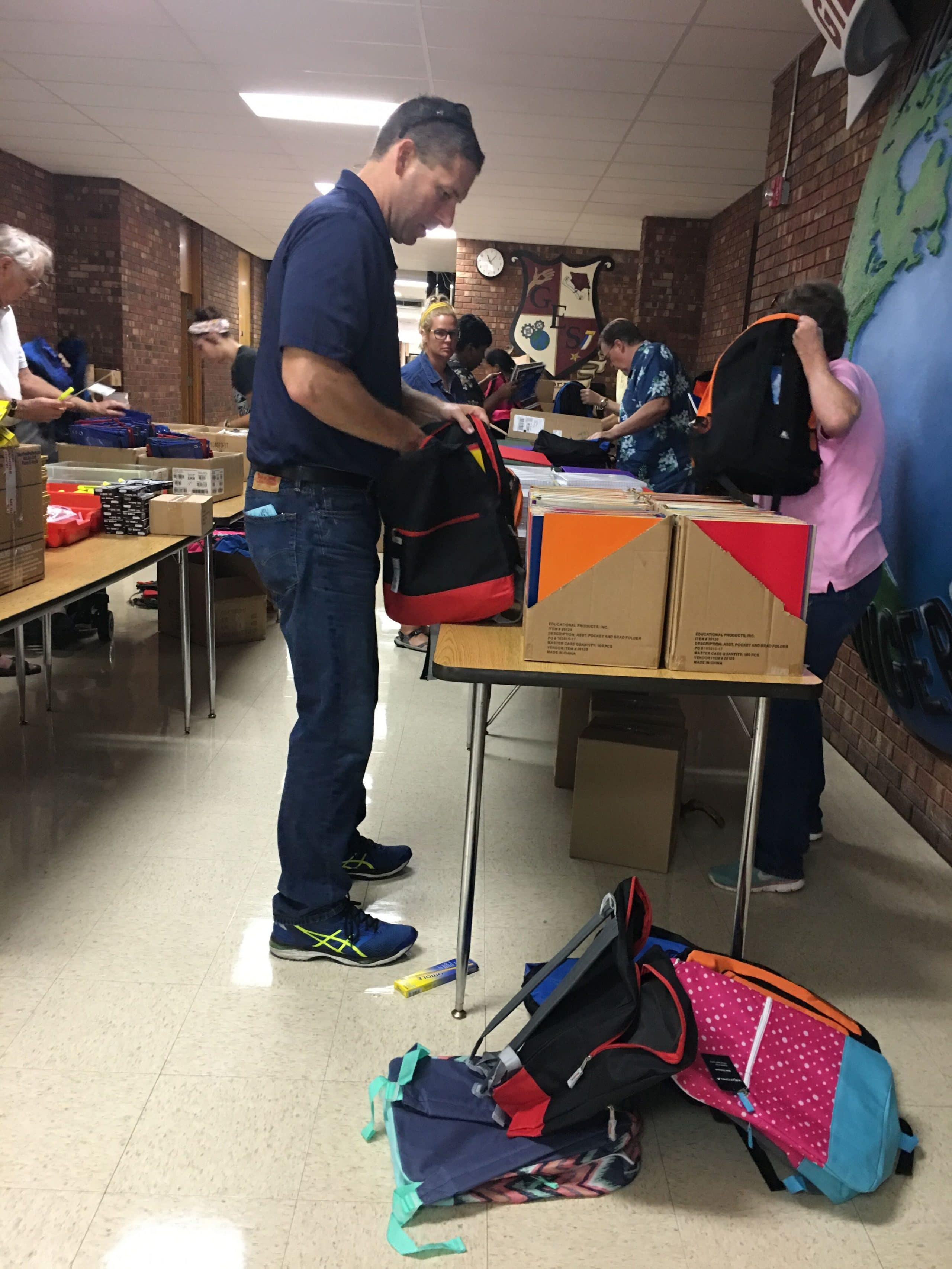 Attorney Chad McLain helps with backpack stuffing