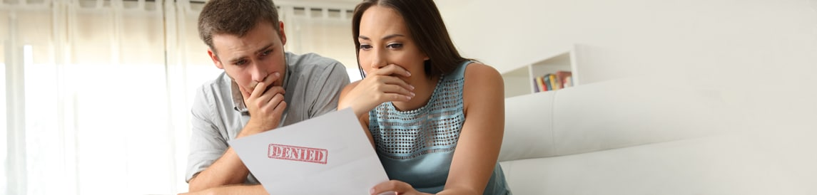 man and woman looking concerned at piece of paper with red stamp on it that says denied