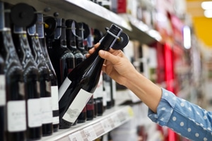 woman selecting wine from shelf