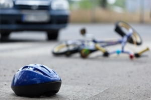 bike helmet on road with bicycle laying in background