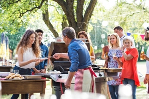 man serving from barbecue with several people standing nearby