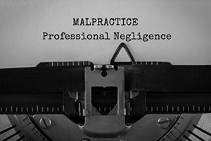 typewriter that has typed out the words Malpractice Professional negligence