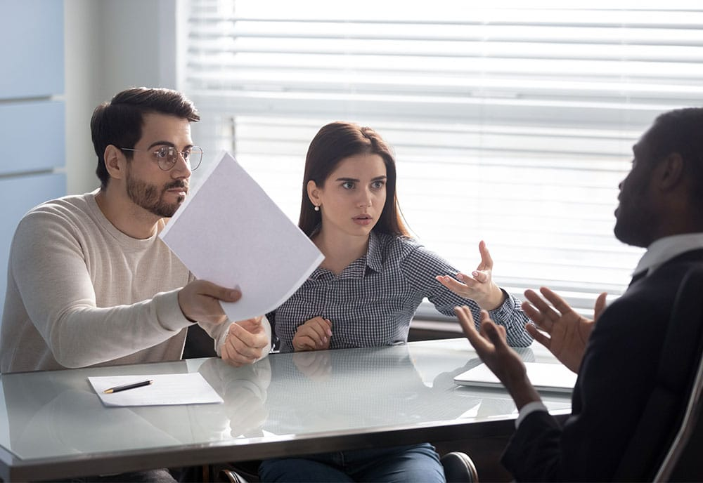 Annoyed clients couple arguing with bank manager