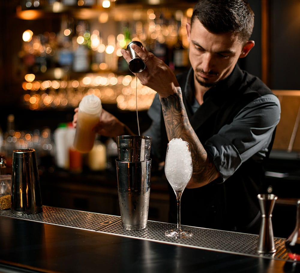 Concentrated male bartender pouring a liqour from the jigger to a professional steel shaker on the bar counter