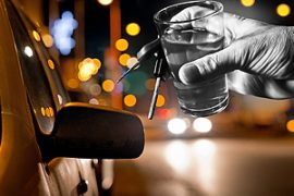 hand holding glass of liquor and car keys outside of a parked car